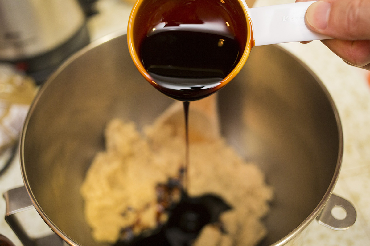 Adding molasses to the sugar mixture.